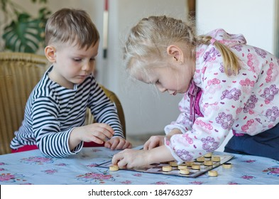 Young girl and boy playing checkers or draughts together with the little girl bending over the board moving her counters watched closely by her brother