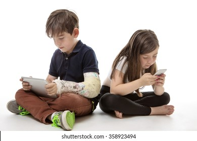 a young girl and boy playing on their tablet computer and mobile phone