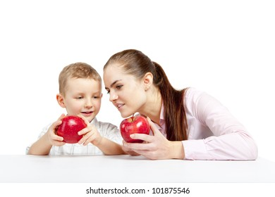 A young girl and boy sitting and watching the apples that will they eat for the moment.