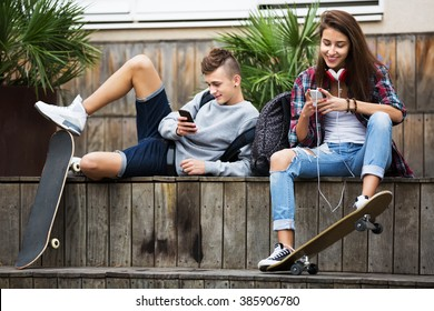 Young girl and boy teens playing on mobile phones and listening to music outdoors