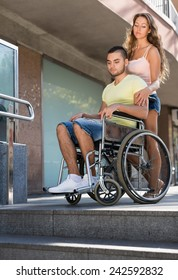 Young girl and boyfriend  in invalid chair near undercrossing