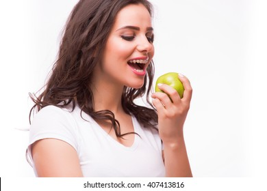 Young girl with brances eat apple. Female teeth with dental braces and apple. Healthy eating with braces