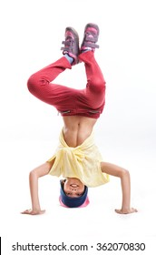 Young girl break dancer performing headstand against white