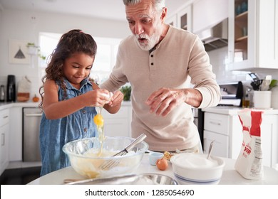 Young girl breaking an egg into cake mixture with her grandfather at the kitchen table, close up