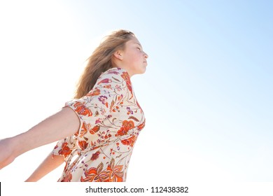 Young girl breathing fresh air while enjoying the sun on a golden sand beach with a blue sky and the sea horizon in the background.
