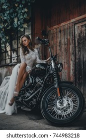 Young girl bride on a new man's motorcycle. Waiting for his prince