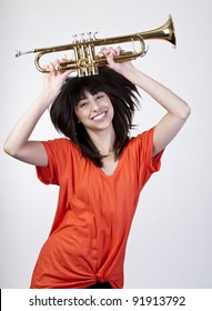 Young girl with bright orange shirt with hair flying and holding a brass trumpet over her head