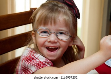 A young girl with a bright smile and crooked, thick glasses.  Her eye has strabismus from ocular palsy from a vaccine adverse reaction.  One eye turns out a bit.  She has a drink stain on her lip.