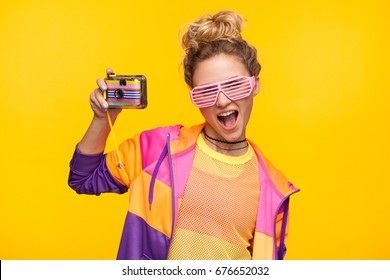 Young girl in bright sportive clothing and sunglasses posing with photo camera.