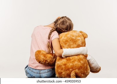 Young girl with broken arm is holding a soft toy bear.