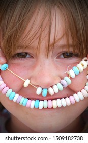 A young girl with brown eyes and freckles holding a candy necklace over her mouth as a smile.