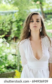 Young girl with brown hair down wearing a white wedding dress with deep neckline and white earrings. Picture taken outdoors in park after rain.