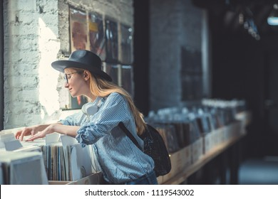 Young girl browsing vinyl records in a music store
