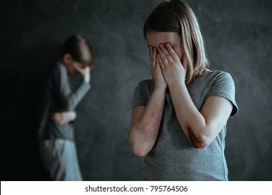 Young girl with bruises and boy crying alone in the dark room