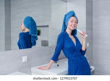 young girl brushing her teeth with an electric toothbrush in the bathroom.