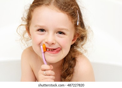 Young girl brushing her teeth and sticking tongue