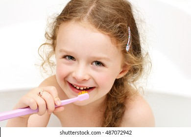 Young girl brushing teeth while sitting in the bath and smiling