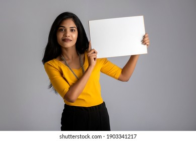 A young girl or businesswoman holding a signboard in her hands on a gray background.
