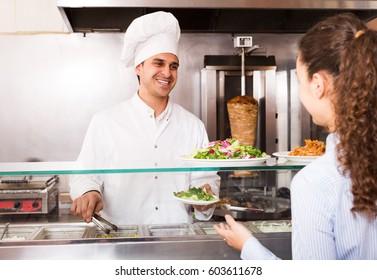 Young girl buying kebab and salad at counter