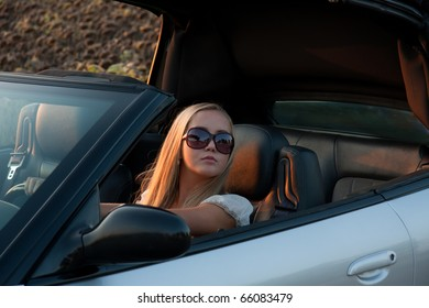 young girl in cabrio car, on sunset light