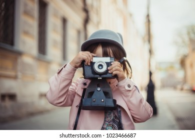 Young girl with camera walking on Moscow street at sunny day