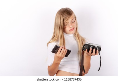 Young girl cant decide between smartphone and compact camera. Mobile phone versus classic camera concept