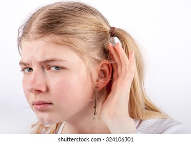 Young girl can't hear you - she cupping her hand behind her ear and looking very sadly