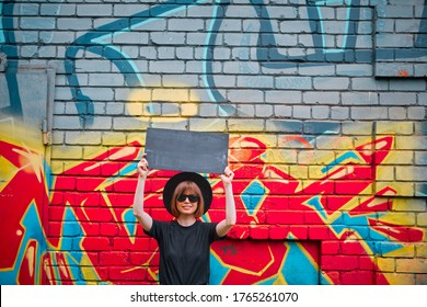 Young girl with cardboard sign of protest above head stand against brick wall with colorful graffiti