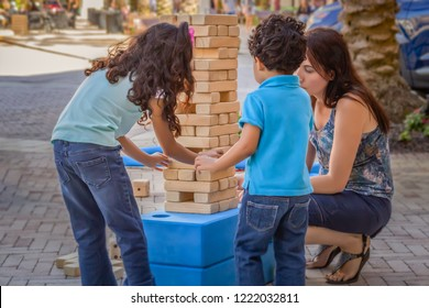 The young girl is careful not to knock down the wooden large size jumbling tower while younger brother waits his turn with mommy. Mom enjoys these precious moments playing with her kids outside.