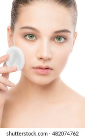 Young girl cares for face skin relaxation. Beautiful young brunette woman with clean perfect fresh skin using cotton pad. Youth and skin care concept. Isolated on a white.