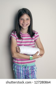 Young girl with a cast on a broken wrist or arm  smiling