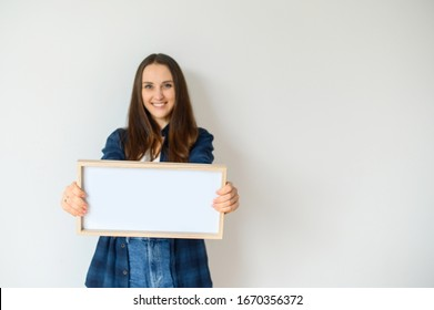 Young girl in casual clothes holding a blank sign in her hands and smiling.