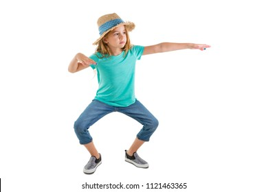 Young girl in casual denim jeans and a straw hat standing making funky dance moves bending at the knee with outstretched arms isolated on white