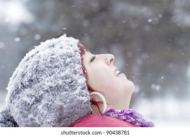 The young girl catches snowflakes