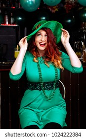 Young girl celebrate St. Patrick's Day. Woman have fun at the bar. A beautiful girl in a green leprechaun hat and dress drinks a green cocktail.