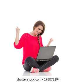 Young girl celebrates success with laptop. Excited young woman is sitting on the floor with legs crossed, holding laptop and smiling with arms raised. Full length studio shot isolated on white.