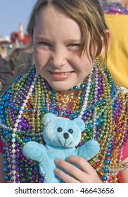 Young girl celebrating Mardi Gras with beads she caught in the parade