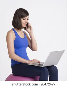 Young girl with cellphone and laptop sitting on exercise ball