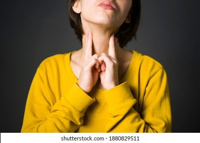 Young girl checks the thyroid gland with her hands, keeps her palms on the neck. Medicine and personal care