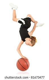 Young girl child balancing upsidedown on top of basketball in uniform over white.