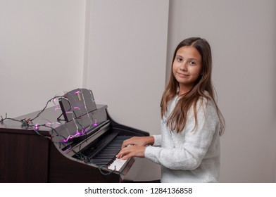 Young girl child plays piano. There are lights on the piano.