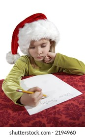 A young girl child writing her wish list to santa. Dear Santa on her otherwise blank piece of paper. Red table cloth, with an isolate white background. Focus on her face with paper out of focus.