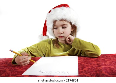 A young girl child writing her wish list to santa. Dear Santa on her otherwise blank piece of paper. Red table cloth, with an isolate white background.
