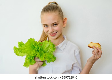 Young girl chooses between a lettuce and baking isolated