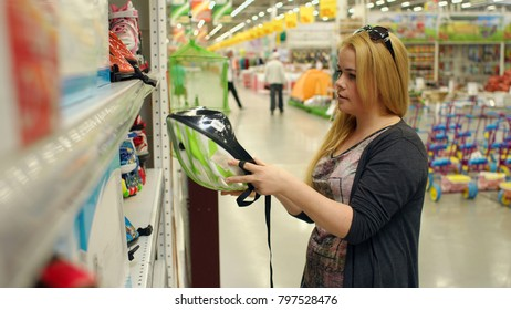 Young girl chooses a Bicycle helmet in supermarket, close-up.