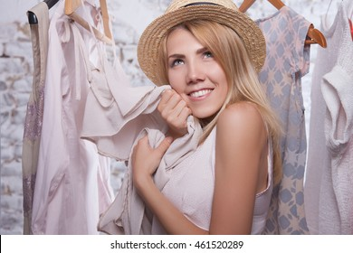 Young girl choosing clothes on sale, happy shopping, natural cloth and comfortable style