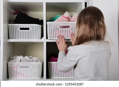 Young girl choosing clothes in wardrobe at home. The wardrobe which put in order. All things are folded neatly. Many boxes. Everything is in its place. Harmony. Concept. Interior. Clothing.