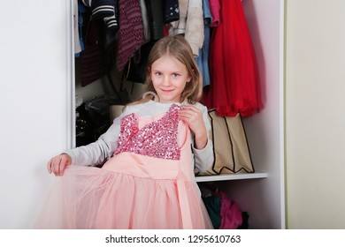 Young girl choosing dress in wardrobe at home. The wardrobe which put in order. All things are folded neatly. Many boxes. Everything is in its place. Harmony. Concept. Interior. Clothing.