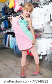 Young girl is choosing modern dress in the shop.
