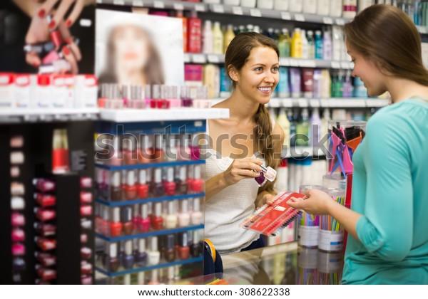 Young girl choosing new nail polish color at store